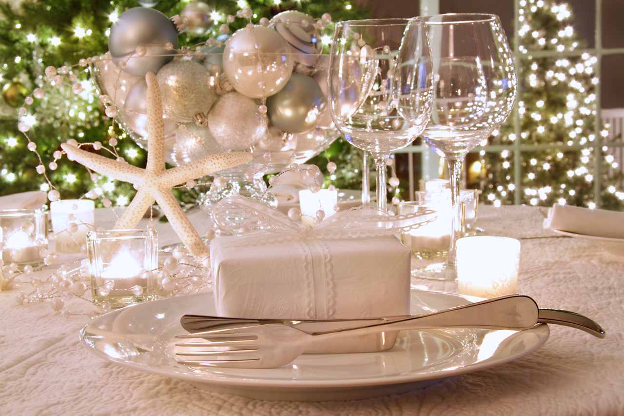 Elegantly lit  holiday dinner table with white ribbon gift